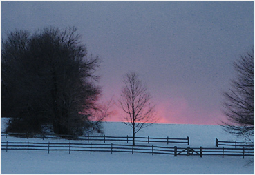 Pink sunlight illuminates snow squalls in the distance.